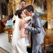 Married couple kissing in orthodox church first time — Stock Photo