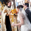 Bride kissing golden crown on orthodox wedding ceremony — Stock Photo