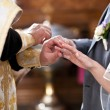 Orthodox bishop putting golden rings on bride and grooms hands — Stock Photo #37195407