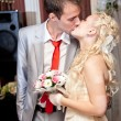 Portrait of blond bride and brunette groom kissing  — Stock Photo