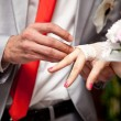Photo of groom putting wedding ring on brides finger — Stock fotografie