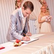 Stock Photo: Groom signing wedding contract during ceremony