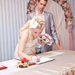 Blonde bride signing wedding contract at wedding office — Stock Photo #37197243
