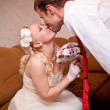 Groom stooping over bride and kissing her — Stock Photo