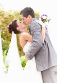 Newly married couple kissing passionately at park — Stock Photo