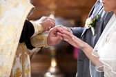 Orthodox bishop putting golden rings on bride and grooms hands — Stock Photo