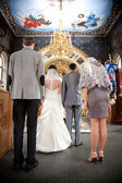 Couple getting married in orthodox church with painted icons — Stock Photo