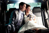 Couple sitting on backseat of the car and looking out of window — Stock Photo