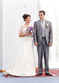 Bride and groom holding hands and standing against white wall — Stock Photo