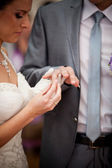 Young bride putting wedding ring on grooms hand — Stock Photo