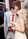 Portrait of blond bride and brunette groom kissing — Stock Photo