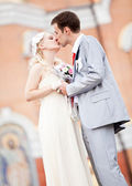 Newly married couple kissing on street at summer — Stock Photo