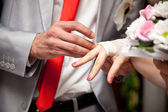 Photo of groom putting wedding ring on brides finger — Stock Photo