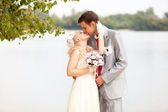 Just married couple kissing passionately on riverbank — Stock Photo