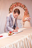 Groom signing wedding contract during ceremony — Stock Photo