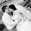 Portrait of bride and groom kissing on hill against old fort — Stock Photo