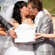 Hands holding white isolated board in front of kissing newlyweds — Stok fotoğraf