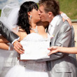 Hands holding white isolated board in front of kissing newlyweds — Photo