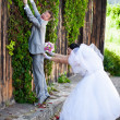 Young groom running away from bride and climbing on high wall — Stock Photo #37456039