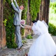 Young groom running away from bride and climbing on high wall — Stock Photo