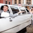 Groom sitting in car while bride pushing it — 图库照片