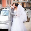 Portrait of bride and groom kissing in front of white limousine — Stock Photo