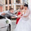 Laughing bride and bridesmaid pulling young groom out of car — Stock Photo