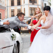 Beautiful bride and bridesmaid pulling groom out of car — Stock Photo #37456091
