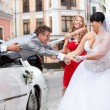 Beautiful bride and bridesmaid pulling groom out of car — Stock Photo
