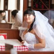 Brunette bride sitting behind table at french restaurant — Stock Photo