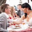 Bride pulling groom by tie and quarreling with him at restaurant — Stock Photo