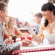 Brunette bride feeding groom from spoon at restaurant — Stock Photo