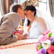 Portrait of newly married couple kissing at restaurant — Stock Photo #37456159