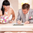 Groom signing wedding contract while bride looking at him — Stock Photo #37456209