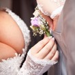 Stock Photo: Bride adjusting boutonniere on grooms grey jacket