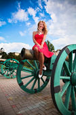 Woman in red dress sitting on old cannon at castle — Stockfoto