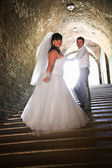 Newlywed couple coming up the stairs at old castle — Stock Photo