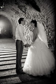 Photo of newlywed couple holding hands in old tunnel — Stock Photo