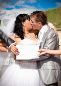 Hands holding white isolated board in front of kissing newlyweds — Stock Photo