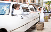 Bride pushing broken white limousine with groom on drivers seat — Stock Photo