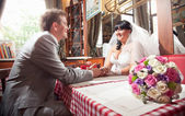 Bride and groom sitting at restaurant and looking at each other — Stock Photo