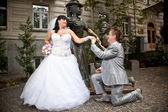 Groom kneeling in front of beautiful bride on street — Stockfoto