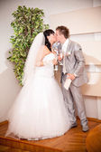 Portrait of newly married couple kissing at wedding office — Stock Photo