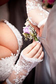 Bride adjusting boutonniere on grooms grey jacket — Stock Photo