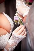 Bride adjusting boutonniere on grooms grey jacket — Stock Photo