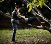Handsome man hugging sexy girl lying on tree branch — Stock Photo