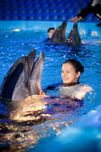 Young woman swimming with dolphin at dolpinarium — Stock Photo