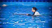 Woman in diving costume swimming in pool with dolphin — Stock Photo
