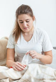 Portrait of sick woman pulling paper tissues from box — Stock Photo