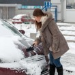 Woman cleaning her car after snow blizzard — Stok fotoğraf